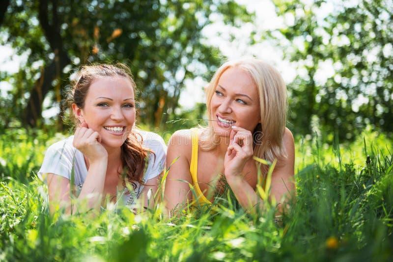 Dos mujeres jovenes lindas que mienten en la hierba en outd del día soleado del verano foto de archivo