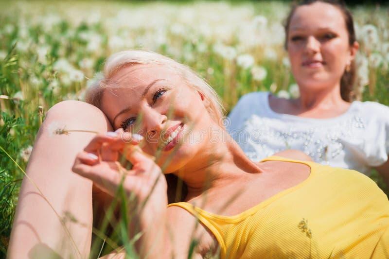 Dos mujeres jovenes lindas que mienten en la hierba en outd del día soleado del verano imagen de archivo