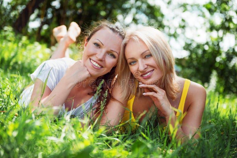 Dos mujeres jovenes lindas que mienten en la hierba en outd del día soleado del verano imagenes de archivo