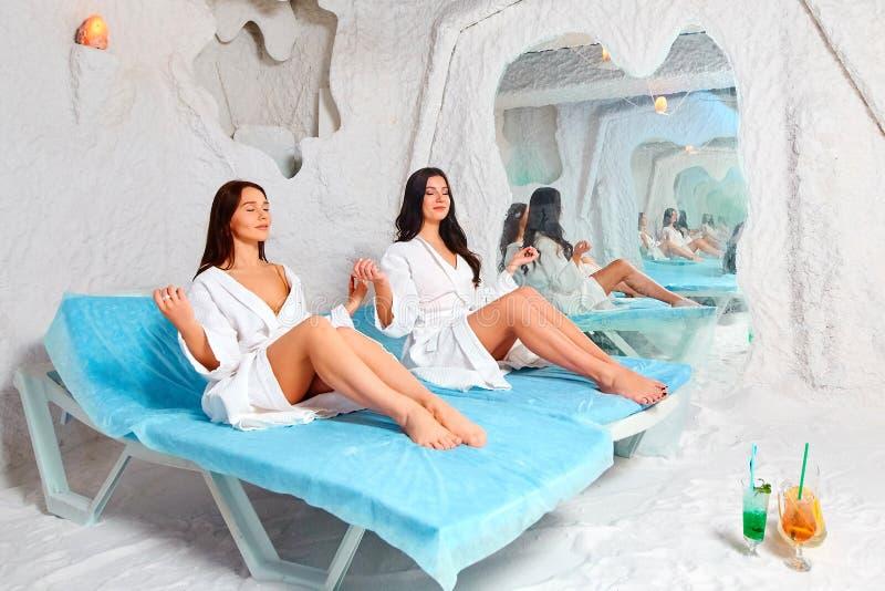 Dos mujeres jovenes meditan en el cuarto de la sal foto de archivo libre de regalías