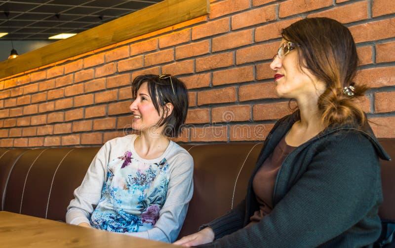 Dos mujeres jovenes morenas que se sientan en un café que tiene conversación foto de archivo