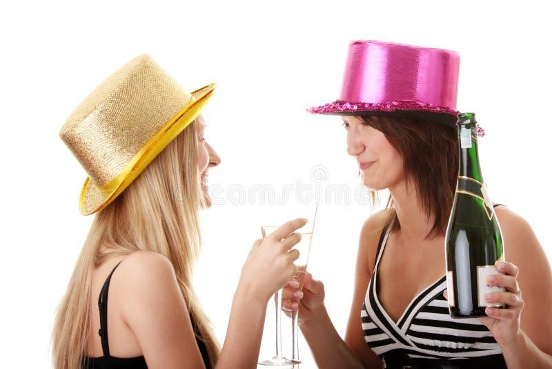 Dos mujeres jovenes ocasionales que gozan del champán imagen de archivo