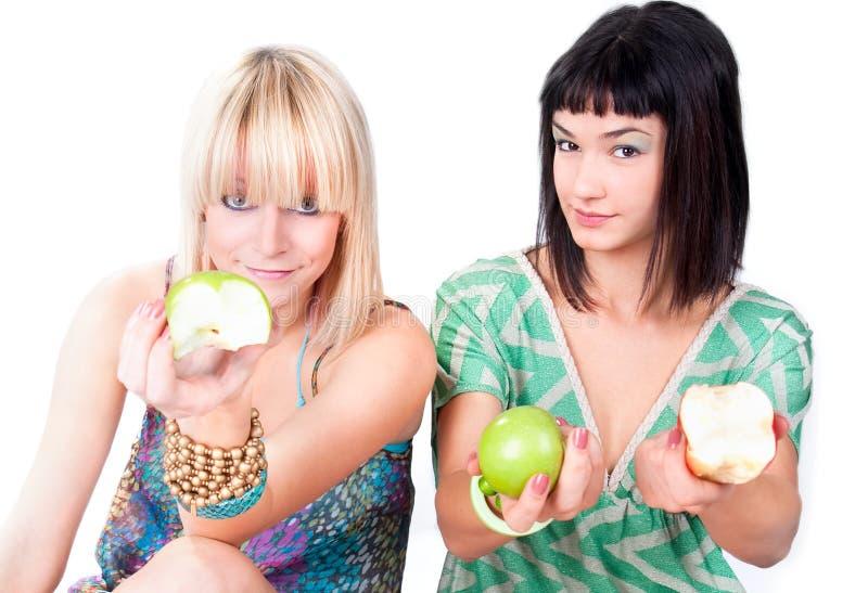 Dos mujeres jovenes ofrecen manzanas verdes fotografía de archivo