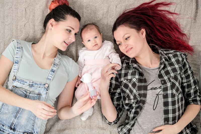 Dos mujeres jovenes, pareja homosexual lesbiana, están mintiendo en una manta con un niño Matrimonio homosexual, adopción imagenes de archivo