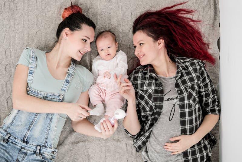 Dos mujeres jovenes, pareja homosexual lesbiana, están mintiendo en una manta con un niño Matrimonio homosexual, adopción imagen de archivo