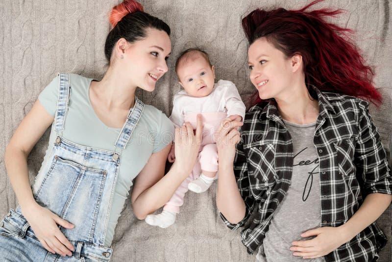 Dos mujeres jovenes, pareja homosexual lesbiana, están mintiendo en una manta con un niño Matrimonio homosexual, adopción foto de archivo