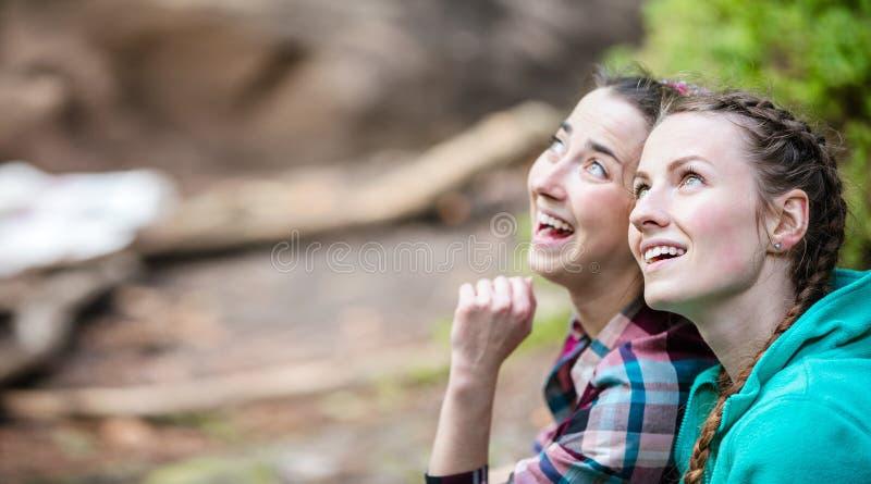 Dos mujeres jovenes que consideran para arriba algo y la sonrisa foto de archivo libre de regalías