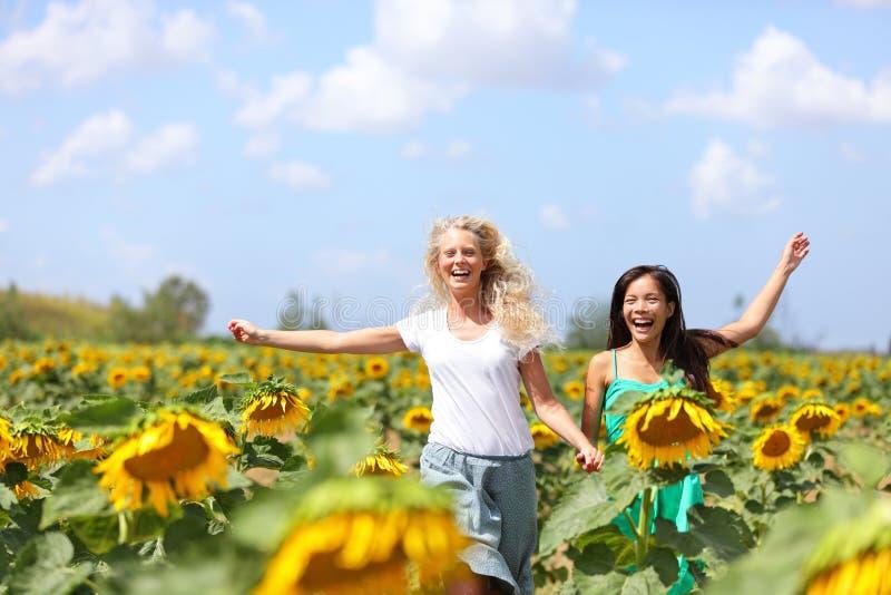 Dos mujeres jovenes que corren a través de los girasoles fotos de archivo