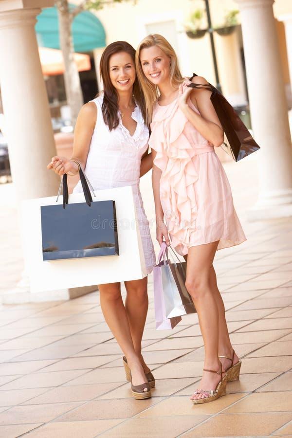 Dos mujeres jovenes que disfrutan de viaje de las compras fotos de archivo