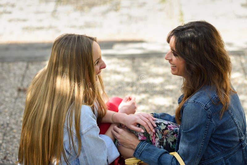 Dos mujeres jovenes que hablan y que ríen en pasos urbanos fotos de archivo