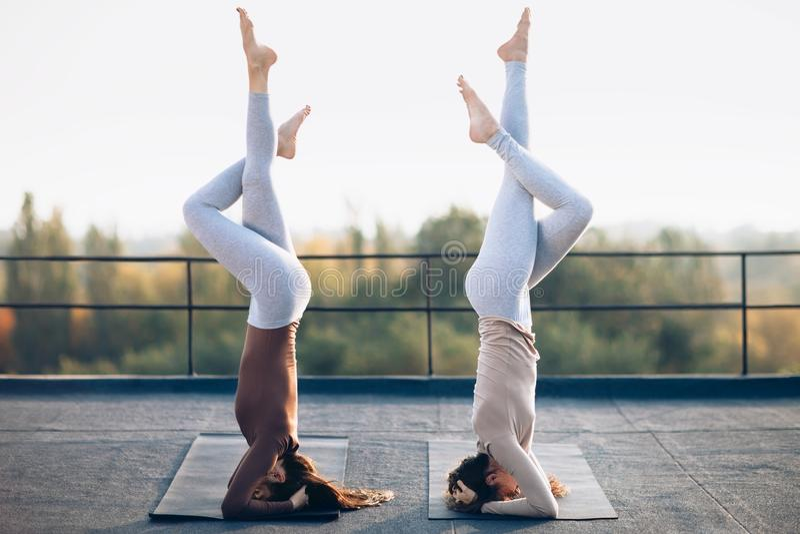 Dos mujeres jovenes que hacían asana doble de la yoga apoyaron el headstand fotografía de archivo