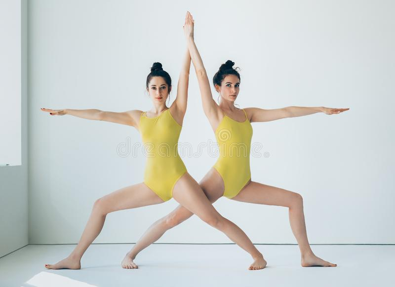 Dos mujeres jovenes que hacen actitud del guerrero II del asana de la yoga foto de archivo