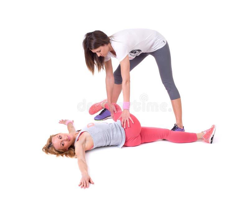 Dos mujeres jovenes que hacen la yoga que estira ejercicios foto de archivo libre de regalías