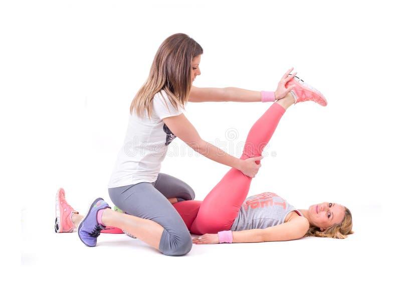 Dos mujeres jovenes que hacen la yoga que estira ejercicios fotografía de archivo libre de regalías