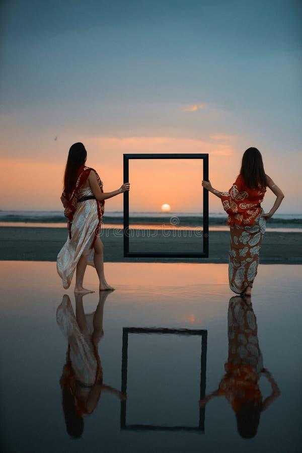 Dos mujeres jovenes que llevan a cabo un marco vacío imagenes de archivo