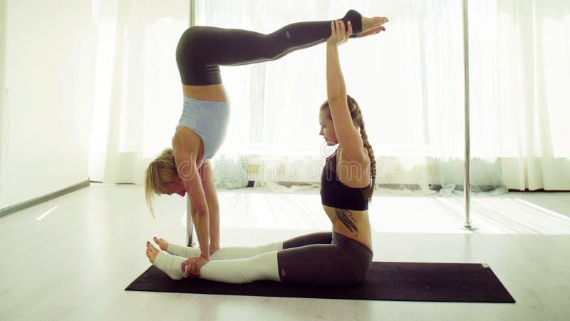 Dos mujeres jovenes que practican yoga acrobática fotos de archivo libres de regalías