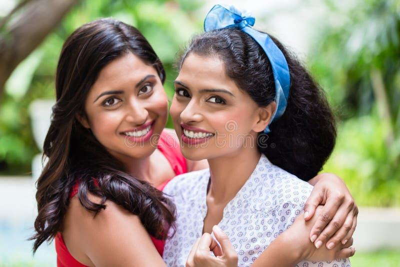 Dos mujeres jovenes que presentan junto como mejores amigos fotografía de archivo libre de regalías