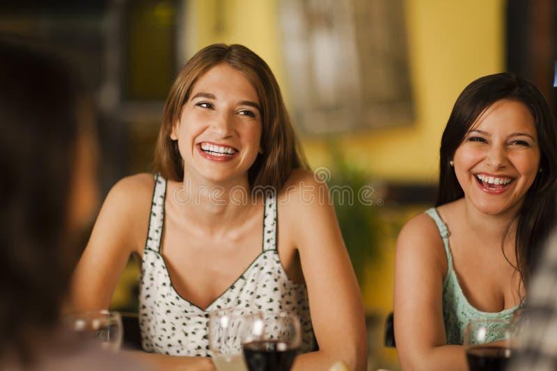 Dos mujeres jovenes que ríen en un restaurante fotos de archivo libres de regalías