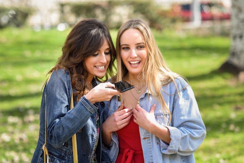Dos mujeres jovenes que registran un mensaje de la voz con el teléfono elegante fotos de archivo libres de regalías