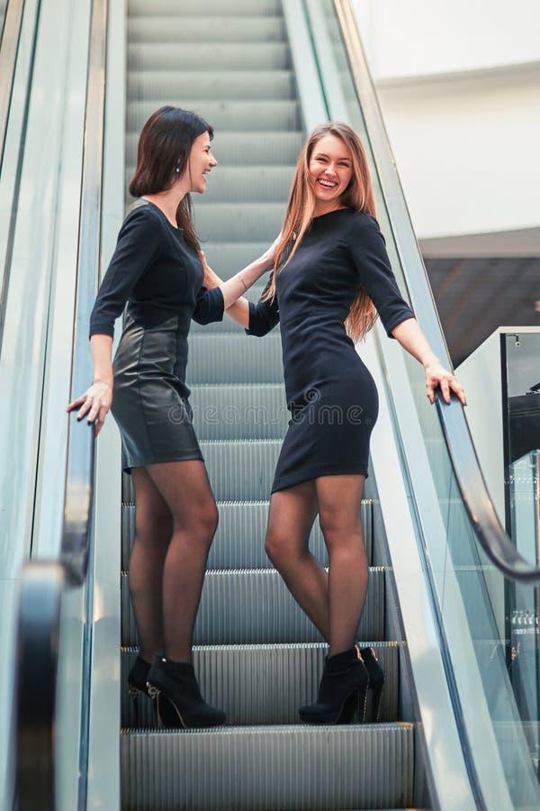 Dos mujeres jovenes que se colocan en los pasos de la escalera m?vil en el centro de negocios foto de archivo libre de regalías
