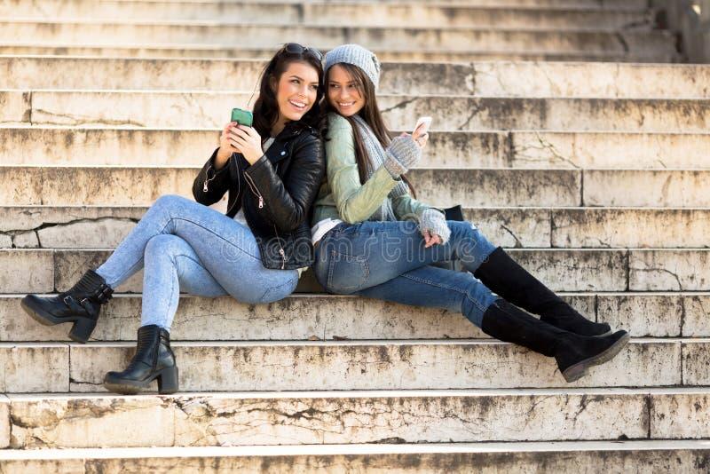Dos mujeres jovenes que se inclinan cara a cara en las escaleras y sostenerse foto de archivo