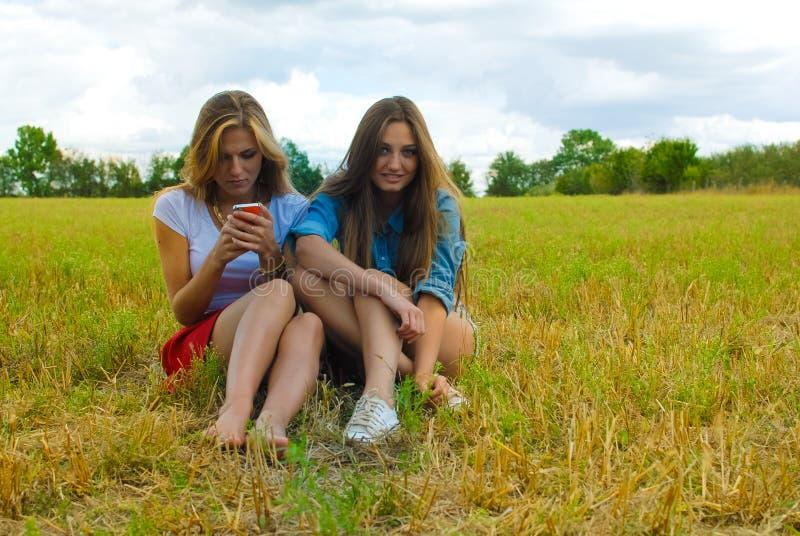 Dos mujeres jovenes que se sientan en la sonrisa del prado del verano foto de archivo