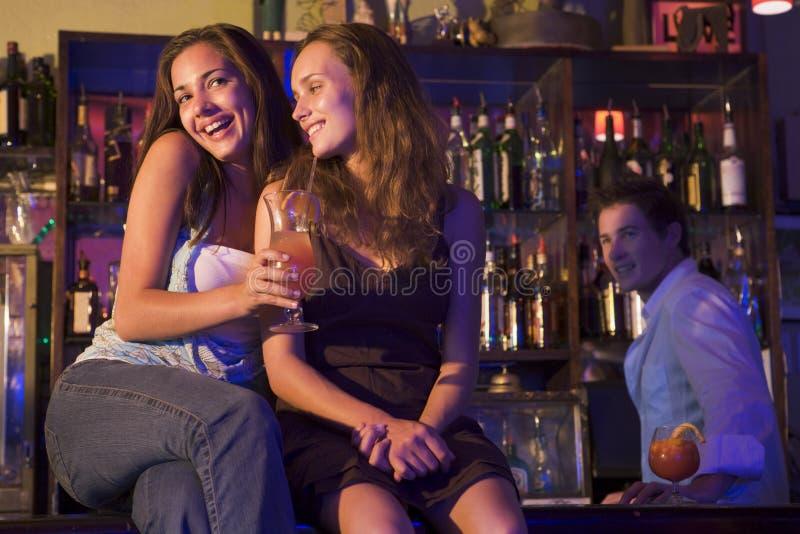 Dos mujeres jovenes que se sientan en un contador de la barra imagen de archivo libre de regalías