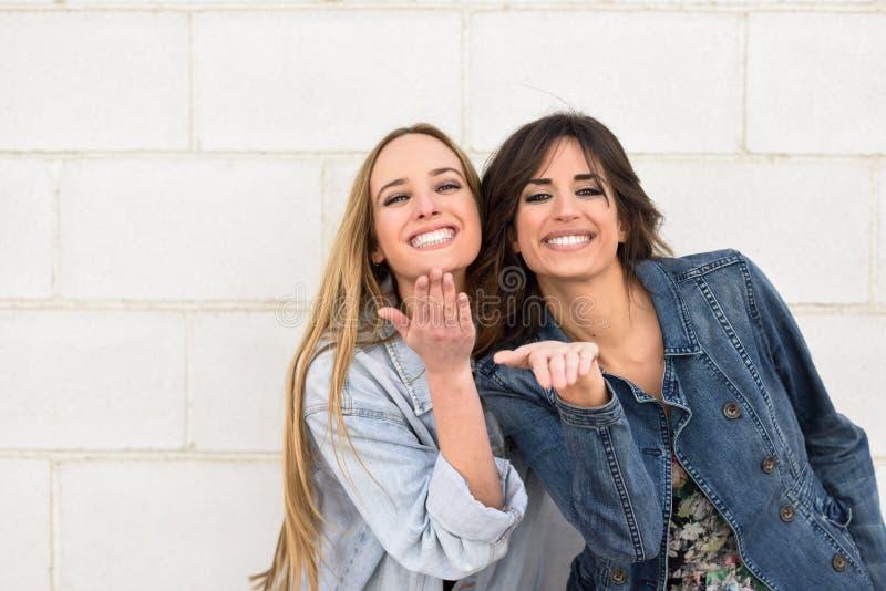 Dos mujeres jovenes que soplan un beso en la pared urbana fotos de archivo