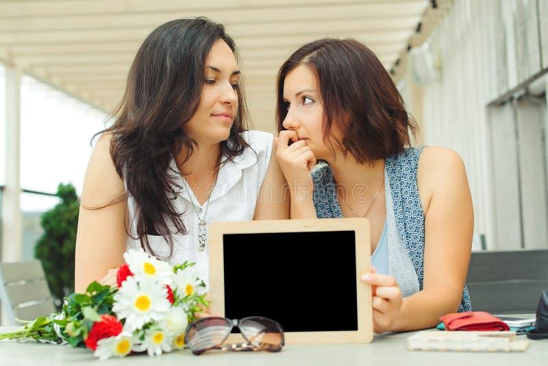 Dos mujeres jovenes que sostienen la pizarra vacía con el marco de madera en el Ca fotografía de archivo libre de regalías