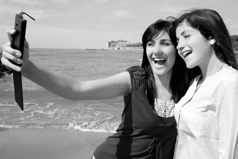 Dos mujeres jovenes que toman el selfie delante de la playa que hace caras divertidas el retrato blanco y negro imagen de archivo libre de regalías