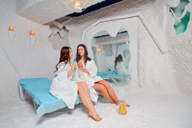 Dos mujeres jovenes relajar y beber una bebida de la vitamina Aplicaci?n de terapia de la sal en el balneario foto de archivo