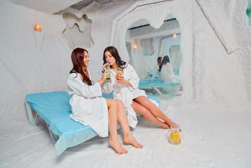 Dos mujeres jovenes relajar y beber una bebida de la vitamina Aplicaci?n de terapia de la sal en el balneario imagenes de archivo