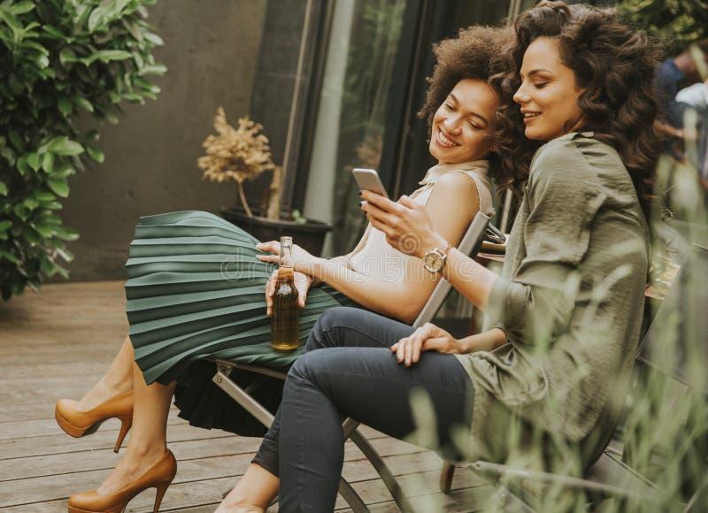 Dos mujeres jovenes se sientan en el fondo que miran en el teléfono móvil a foto de archivo