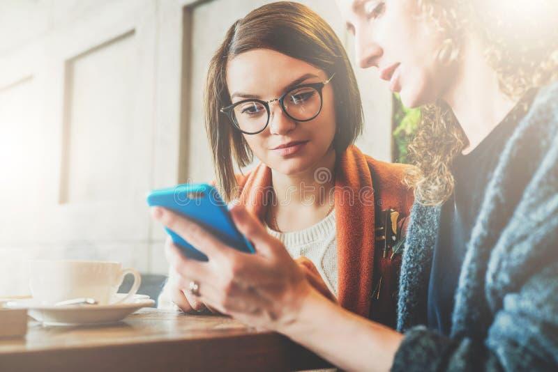 Dos mujeres jovenes se sientan en un café en la tabla y utilizan un smartphone La muchacha muestra a su amigo una imagen en la pa fotografía de archivo libre de regalías
