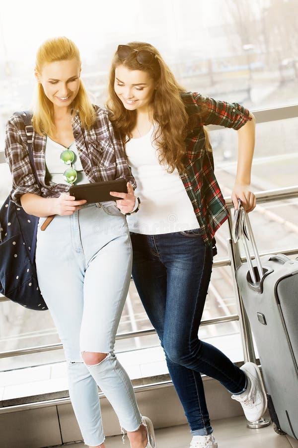 Dos mujeres jovenes turísticas usando la tableta digital fotos de archivo libres de regalías