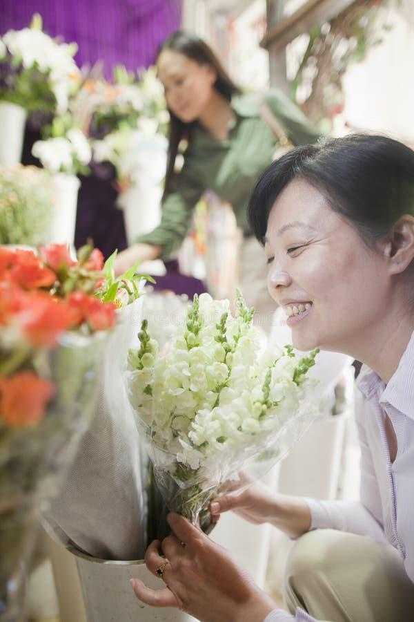 Dos mujeres maduras que miran las flores en floristería foto de archivo