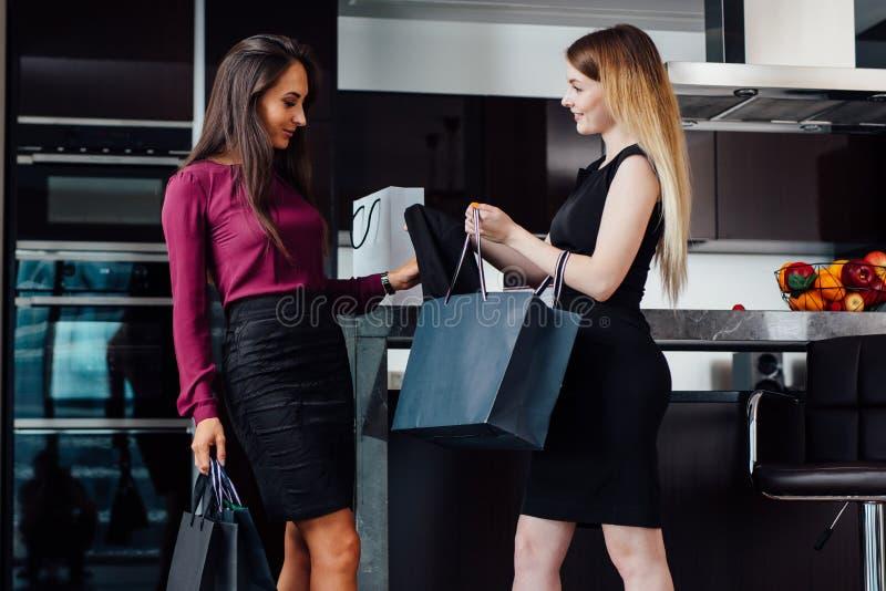 Dos mujeres magníficas después de hacer compras en casa Una muchacha que muestra sus compras a un amigo femenino que se coloca en fotos de archivo libres de regalías