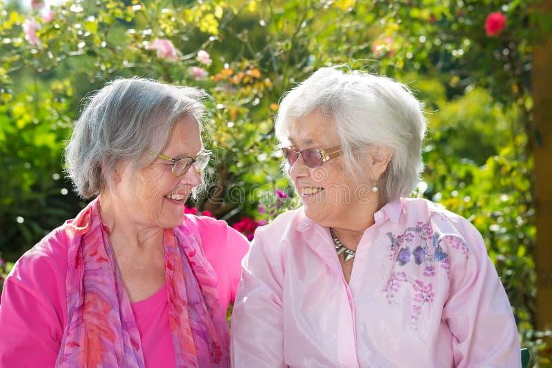 Dos mujeres mayores alegres que se relajan en jardín fotos de archivo