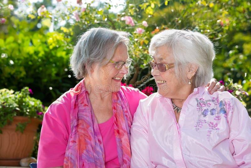 Dos mujeres mayores felices que charlan en jardín imagen de archivo libre de regalías