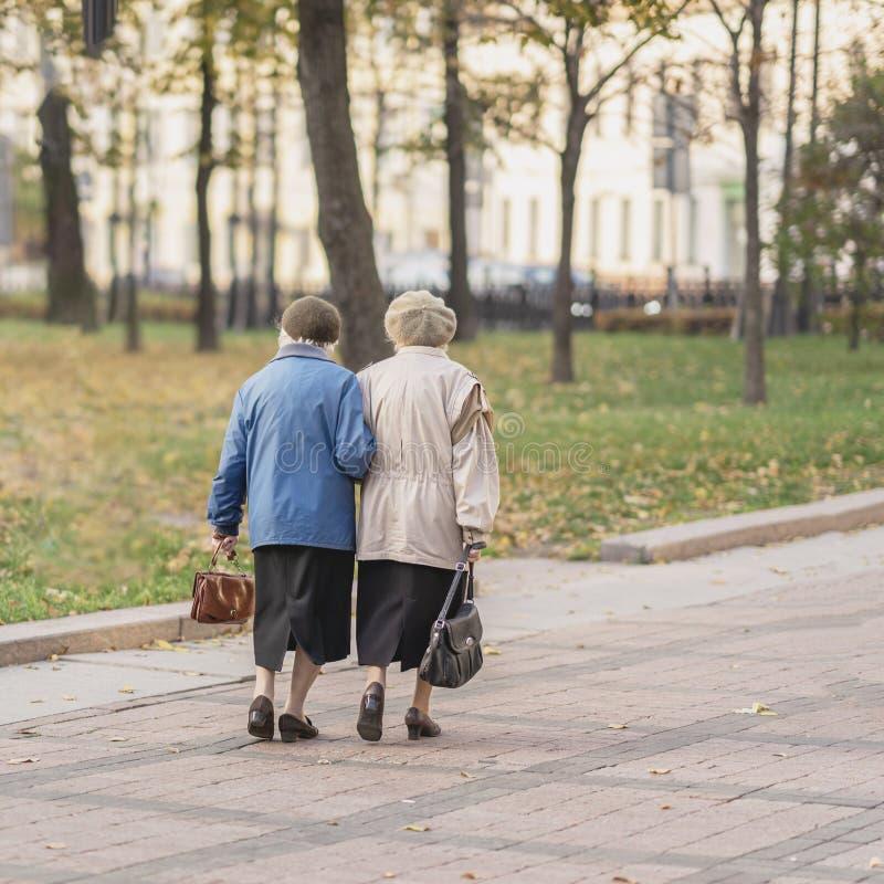 Dos mujeres mayores irreconocibles que caminan junto en la ciudad, pensionistas Otoño, tiempo, intereses mayores, estilo de vida imagen de archivo libre de regalías