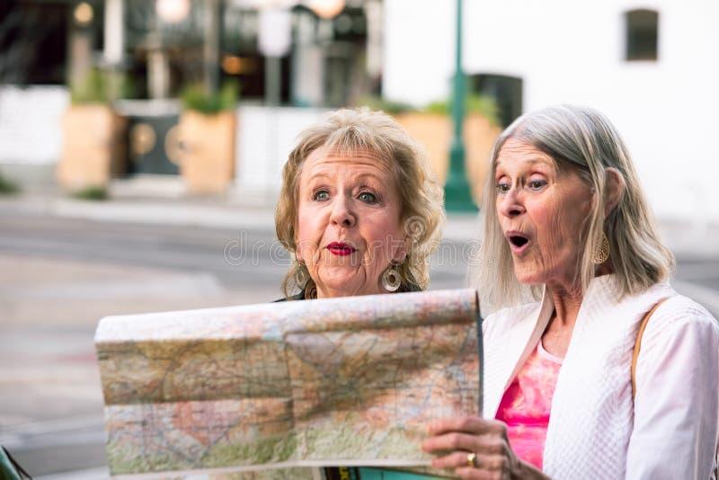 Dos mujeres mayores que comprueban un mapa imagen de archivo