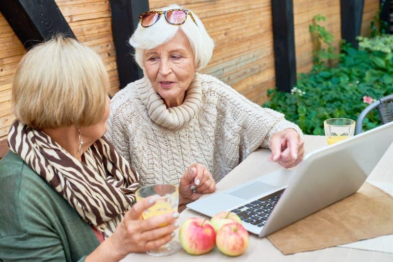 Dos mujeres mayores que usan el ordenador portátil al aire libre fotos de archivo
