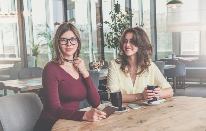 Dos mujeres morenas jovenes atractivas se sientan en café en la tabla y beben el café Amigos de la reunión en el restaurante imagen de archivo