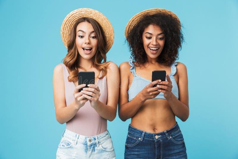 Dos mujeres multiétnicas del verano que llevan la expresión de los sombreros de paja excit fotografía de archivo