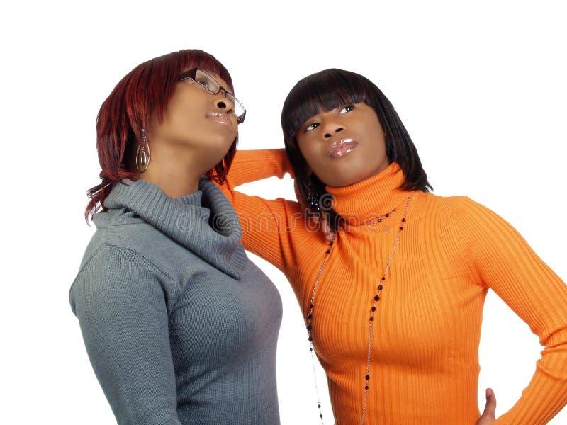 Dos mujeres negras en los suéteres que miran para arriba imagen de archivo libre de regalías