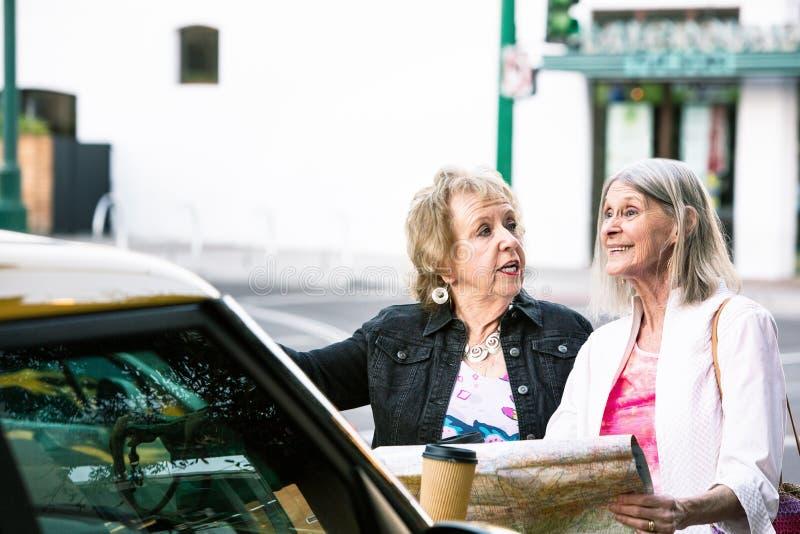Dos mujeres que comprueban direcciones con un mapa de camino imagen de archivo