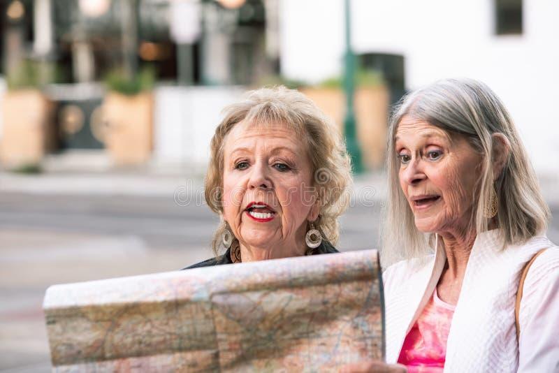 Dos mujeres que comprueban un mapa imagen de archivo libre de regalías