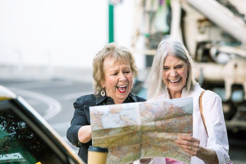 Dos mujeres que comprueban un mapa y una risa fotos de archivo libres de regalías