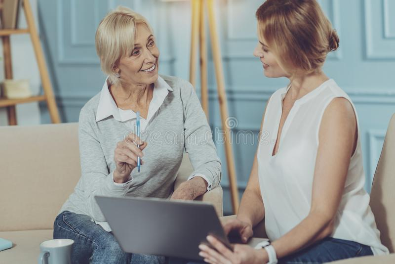 Dos mujeres que discuten negocio usando un ordenador portátil imagen de archivo