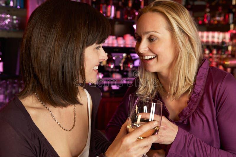 Dos mujeres que disfrutan de la bebida junto en barra imagenes de archivo
